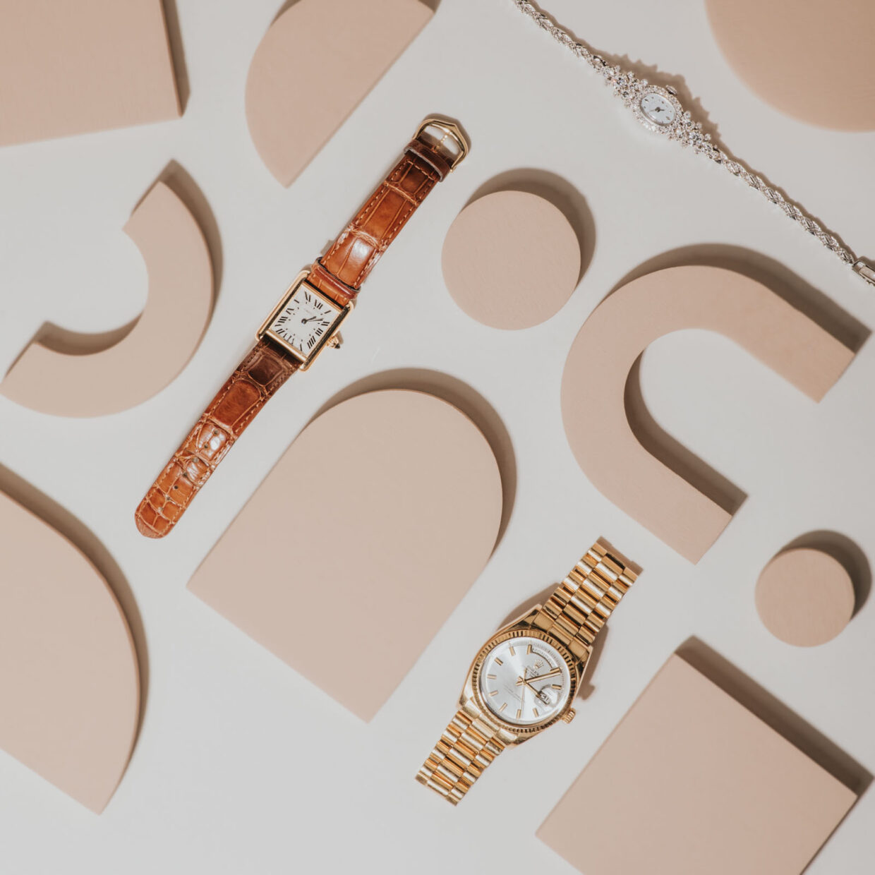 creative photoshoot for jewelry. Layflat ideas for professional photography. 3 watches. One with diamond encrusted band, another with gold links, and last with walnut leather band. Cartier and Rolex watches