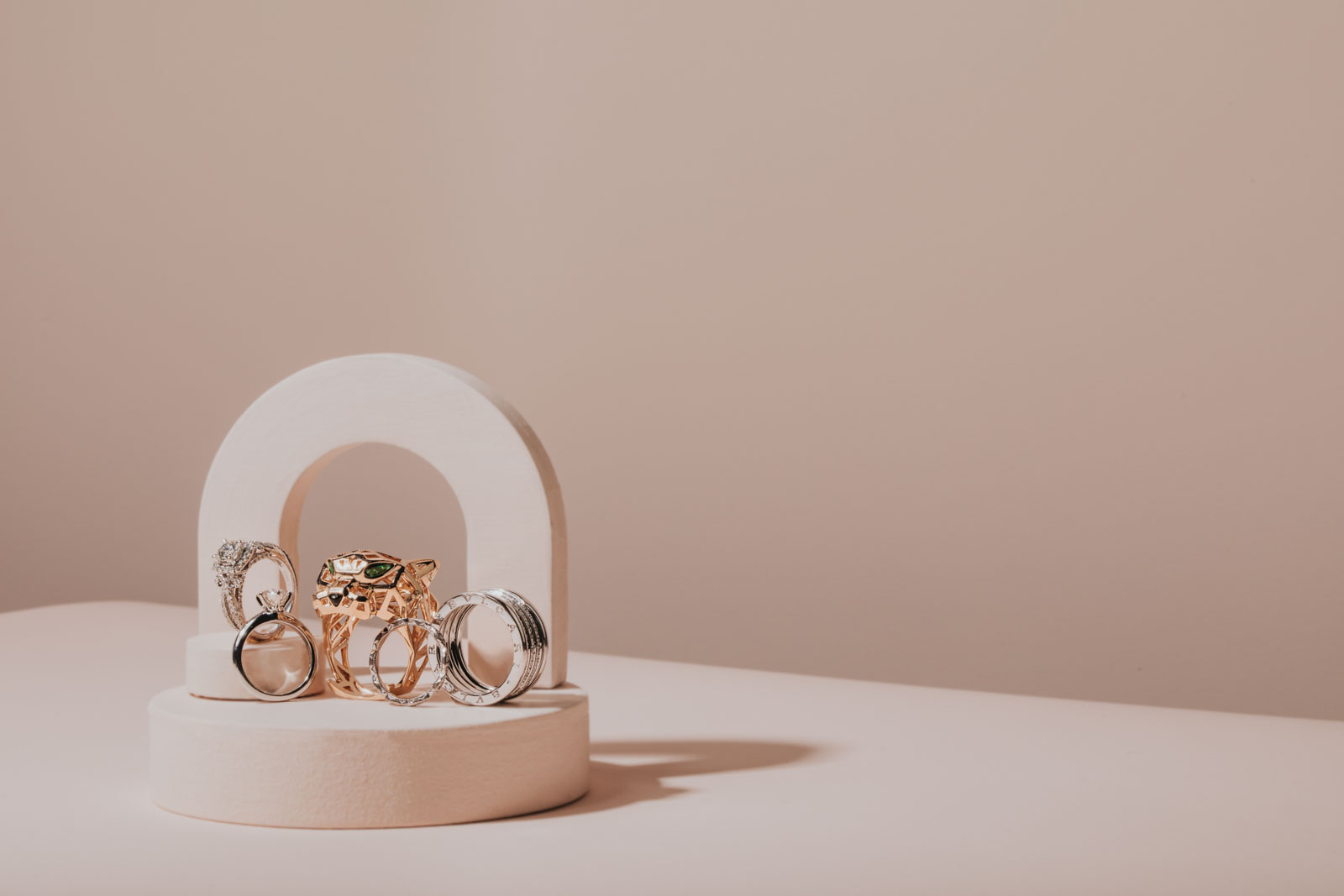 Fun and creative product photography for jewelry. Cartier gold panther ring with emerald eyes and bvlgari diamond wedding band. Diamond engagement ring by Tiffanys. Light pink and blush setup for commercial e-comm photoshoot