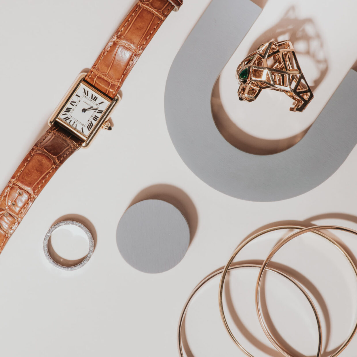 Simple gold bracelets. Birks diamond wedding band. Cartier leather classic watch. Cartier Gold Panther ring with emerald eyes. Professional and creative layflat jewelry photograph