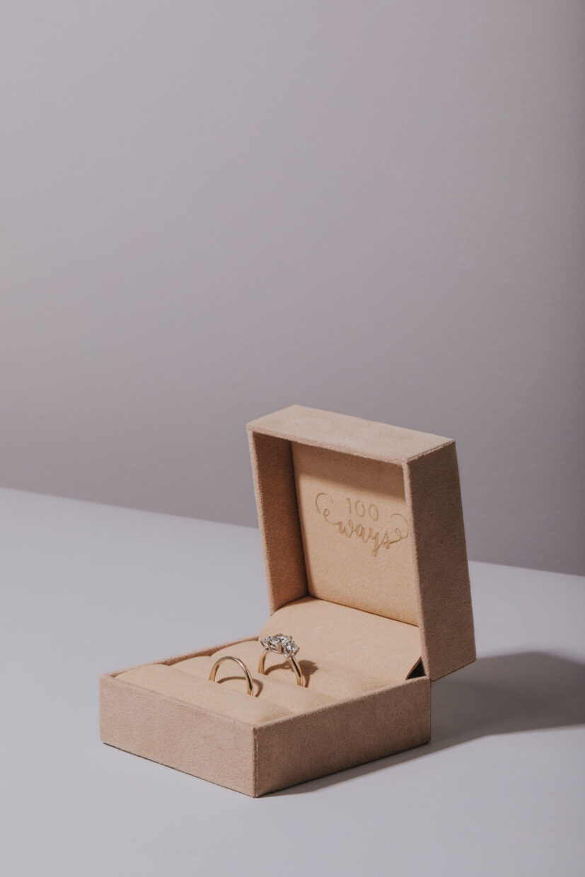 Professional photograph of a jewelry box with a diamond engagement ring inside. Blush coloured velvet wrapped jewelry box with vintage gold rings. Professional product photography
